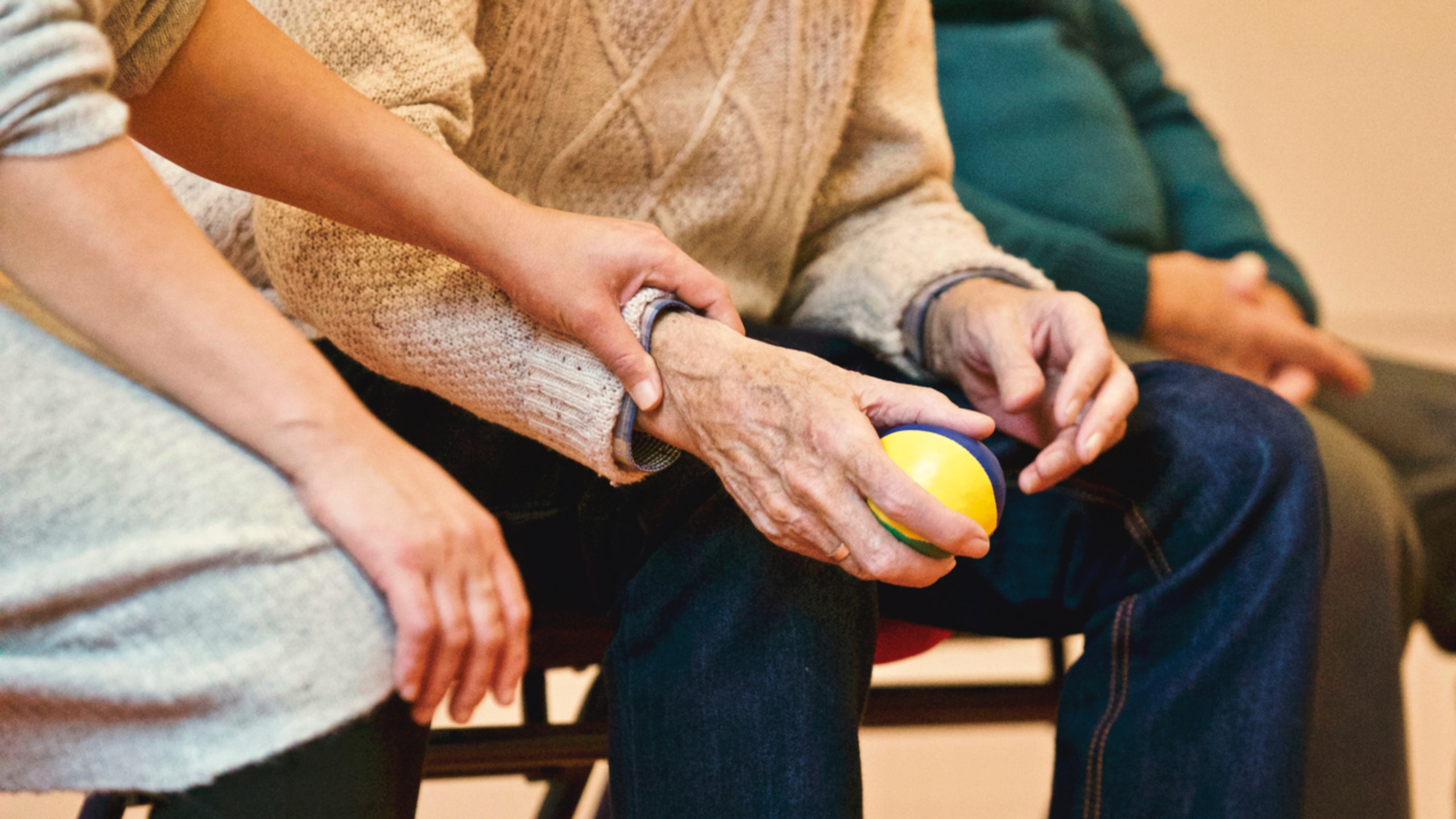 Older adult gripping a ball with another person gently holding his arm.